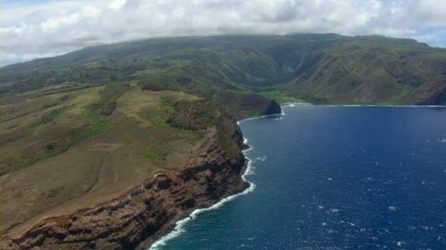 A lush valley slopes toward the ocean on the island of Maui.
