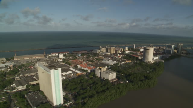 lush vegetation borders high rises on the coast of recife, brazil. - recife stock videos and b-roll footage