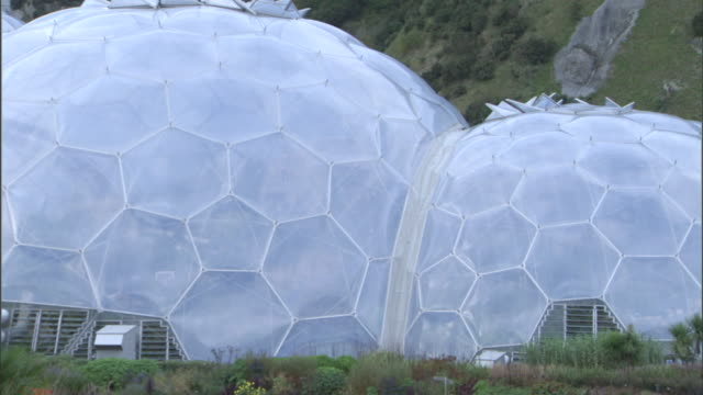 lush vegetation surrounds the biodomes of the eden project in cornwall. - new stock videos & royalty-free footage
