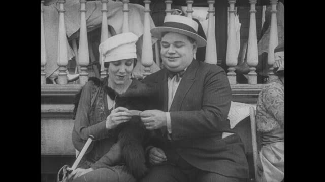 1917 lusting man (fatty arbuckle) gives his calling card to flirtatious woman - flüstern stock-videos und b-roll-filmmaterial