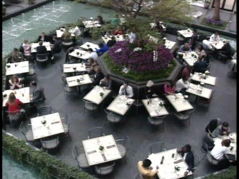 luxurious dining hall area surrounded by fountain pool, people sitting at tables, dining, around octagon shape designed center area w/ plants, tree.... - pool hall stock videos & royalty-free footage