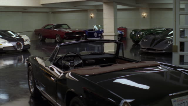 luxury and classic cars reflect off of a shiny floor in a large garage. - expense stock videos and b-roll footage