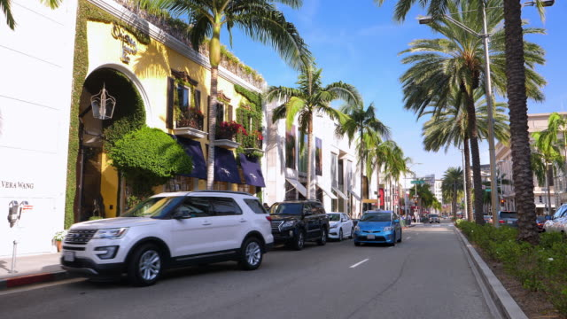 Luxury cars driving on Rodeo Drive near Beverly Wilshire Hotel landmark in Beverly Hills, Los Angeles, California, 4K
