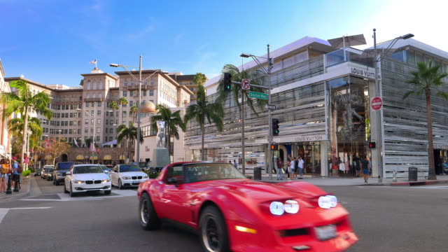 luxury cars driving on rodeo drive near beverly wilshire hotel landmark in beverly hills, los angeles, california, 4k - beverly hills bildbanksvideor och videomaterial från bakom kulisserna
