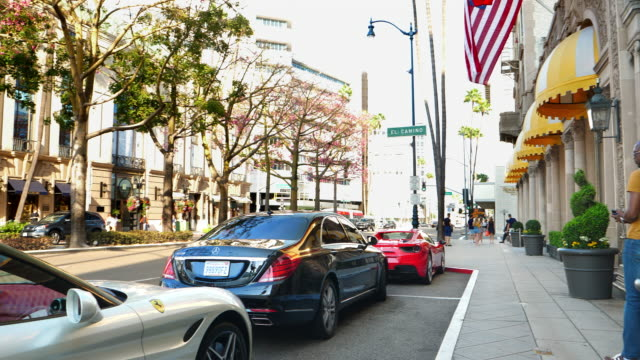 luxury cars parking on rodeo drive near beverly wilshire hotel landmark in beverly hills, los angeles, california, 4k - ビバリーヒルズ点の映像素材/bロール