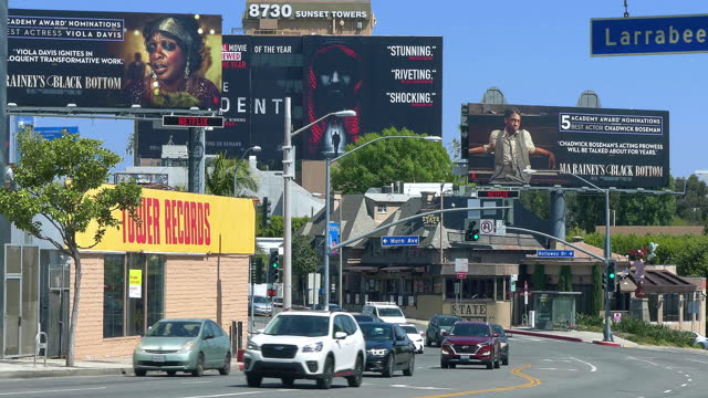 luxury cars traffic on sunset strip on sunset boulevard at rush hour near giant movie billboards in los angeles, california, 4k - beverly hills california stock videos & royalty-free footage