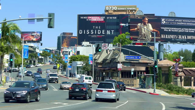 luxury cars traffic on sunset strip on sunset boulevard at rush hour near giant movie billboards in los angeles, california, 4k - street name sign stock-videos und b-roll-filmmaterial