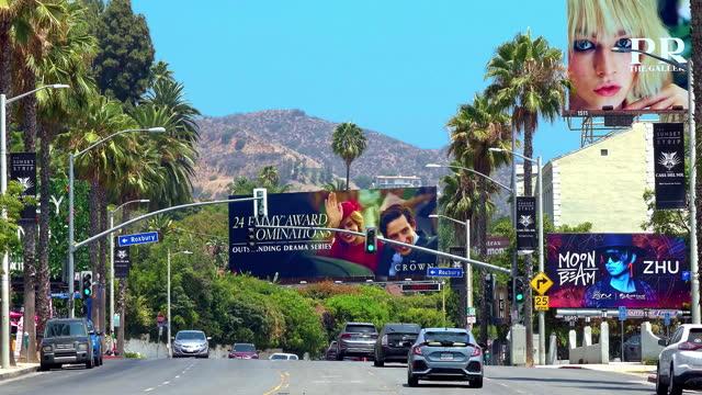 luxury cars traffic on sunset strip on sunset boulevard at rush hour near giant movie billboard in los angeles, california, 4k - rush hour 2 bildbanksvideor och videomaterial från bakom kulisserna