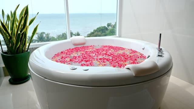 vidéos et rushes de baignoire en céramique de luxe avec la fleur colorée dans l'eau avec la vue de mer - eau dormante
