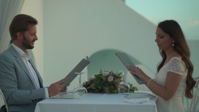luxury couple choosing from restaurant menu