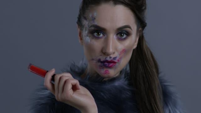 luxus-mode-modell in fell hält roten lippenstift. mode video. - lippenstift stock-videos und b-roll-filmmaterial