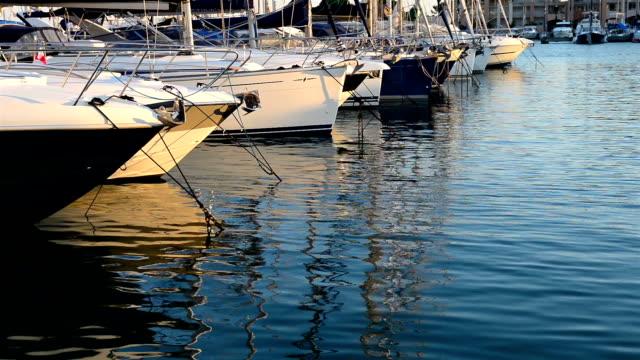 vídeos de stock e filmes b-roll de flutuante iates de luxo no porto - ancorado