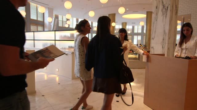 vídeos de stock e filmes b-roll de luxury hotels in miami florida us on december 7 wide shots of guests sitting the lobby wide shots of guests entering the dining area wide shot of... - porteiro