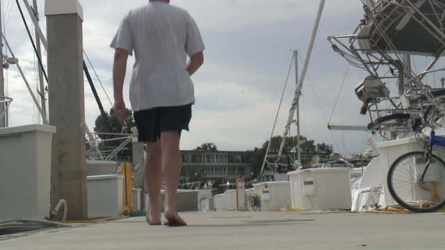 (hd1080i) luxury lifestyle: man on boat dock - leaving - flip flop stock videos and b-roll footage