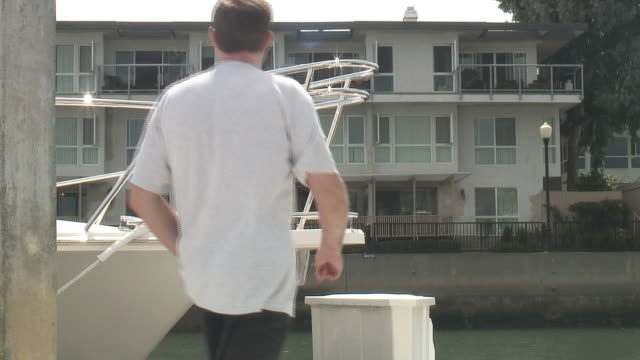 (HD1080i) Luxury Lifestyle: Man on Dock - Passes Boat, Building