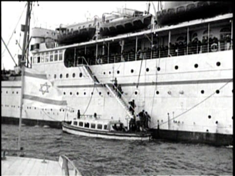 a luxury liner on the ocean shot from the bow / people line the rails looking out / women with children and men sit together in their coats / a... - judaism stock-videos und b-roll-filmmaterial