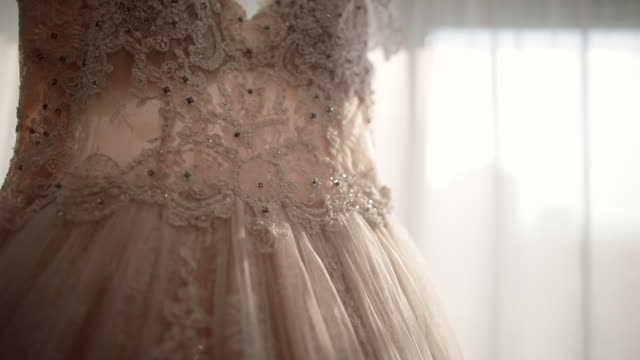 luxury modern wedding dress hanging at window. stylish pastel pink color wedding gown with lace floral details - lace textile stock videos & royalty-free footage