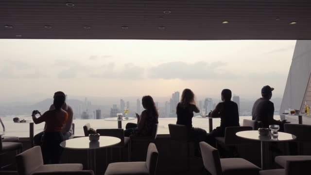Luxury restaurant at a skyscraper top. Lookout to a big capital city at sunset. People silhouettes.