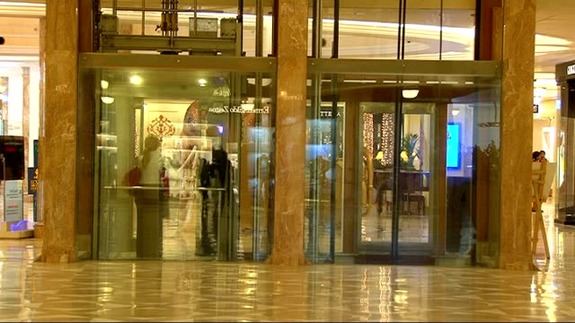 luxury shopping mall gianni versace handbag on display in shop window/ general views of smart walkways and lifts in shopping centre/ clothes and... - south asia stock videos and b-roll footage
