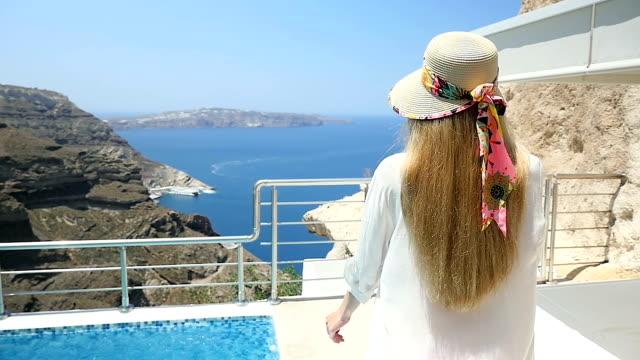 vídeos de stock, filmes e b-roll de férias de luxo & mulher caminhando na varanda - santorini