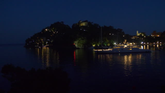 a luxury yacht anchored at night in a resort town in italy, europe. - slow motion - zeus stock videos and b-roll footage