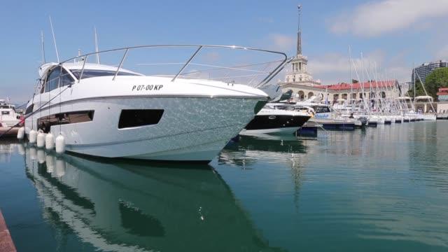vídeos y material grabado en eventos de stock de luxury yachts and motor cruisers sit moored near the quayside in the black sea port of sochi russia on monday may 2 2016 - sochi