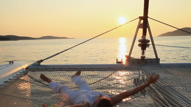 HD: Lying On The Catamaran's Trampoline At Sunset