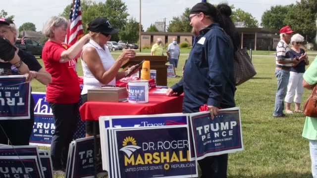 lyon county republicans buying yard signs, hats, flags, t-shirts, buttons from vendors at the local fairgrounds supporting the re-election of... - キャンペーンバッジ点の映像素材/bロール
