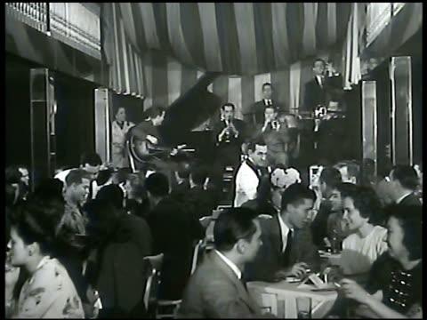 lyons column w/ pencil underlining eddie condon's name. vs int eddie's club jazz musicians on stage crowded nightclub people drinking smoking. waiter... - jazz stock videos & royalty-free footage