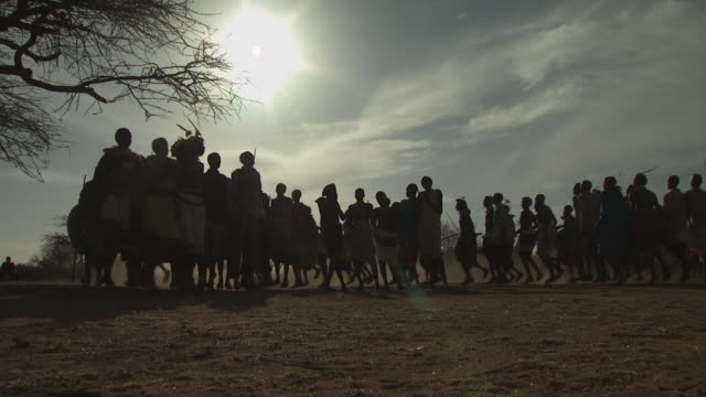 Maasai Ceremony - Warriors dancing in circle, low angle medium shot, silhouetted, WITH AUDIO