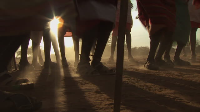 Maasai Ceremony - Warriors dancing, low angle view feet jumping, silhouetted by sun, WITH AUDIO
