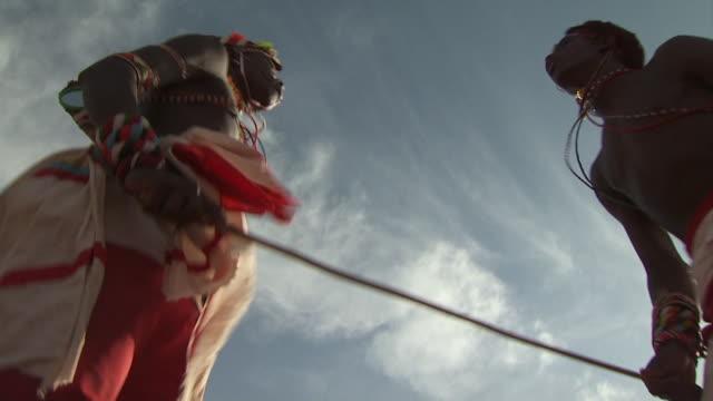 maasai ceremony - warriors jumping up and down, dancing, low angle close up - krieger menschliche tätigkeit stock-videos und b-roll-filmmaterial