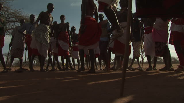Maasai Ceremony - Warriors jumping up and down, dancing, low angle view, WITH AUDIO
