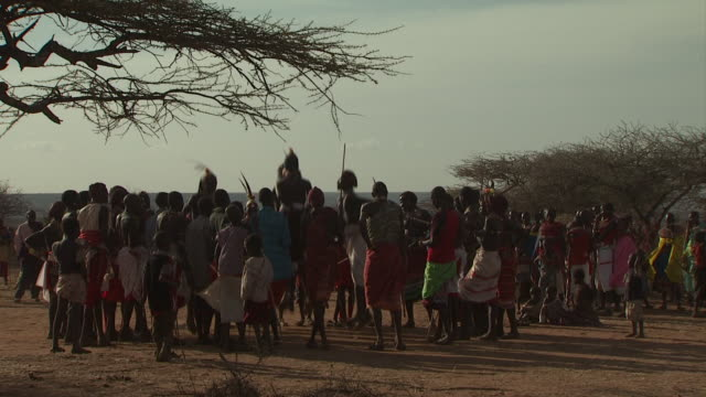 Maasai Ceremony - Warriors jumping up and down, dancing, medium shot group, WITH AUDIO