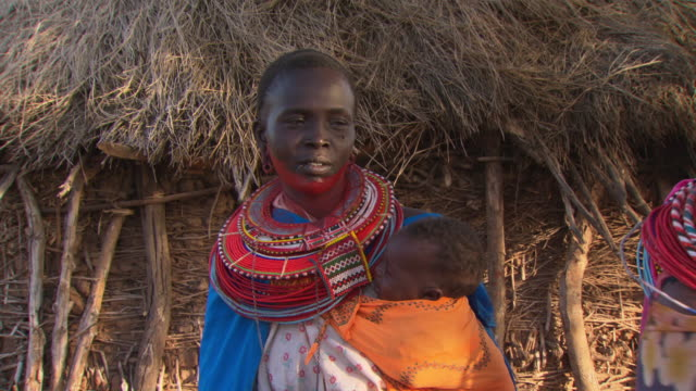 Maasai Ceremony - Women apply red face paint in preparation for ceremony, WITH AUDIO
