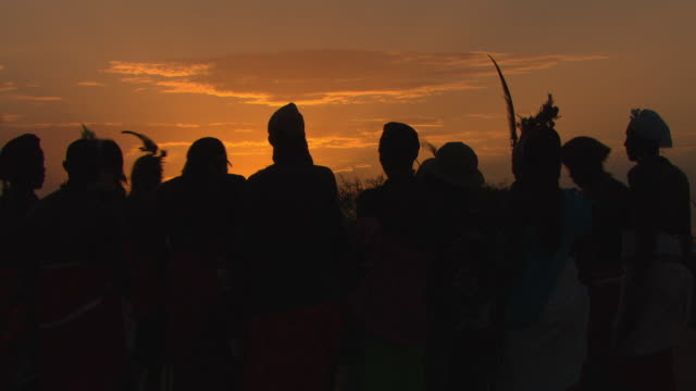 Maasai Ceremony - Young warriors dancing, singing silhouetted at sunset, WITH AUDIO