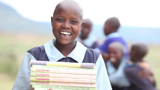 a maasai girl holds a stack of books as children play behind her. - kenya stock videos & royalty-free footage
