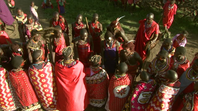vidéos et rushes de maasai men dance as others sing, dance, and play musical instruments in africa. - objet manufacturé