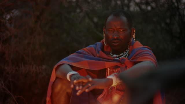 maasai men sit round a campfire, tanzania - minority groups stock videos & royalty-free footage
