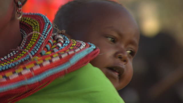 Maasai or Samburu Baby in sling on mothers back, close up, WITH AUDIO