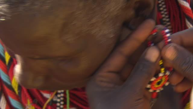 Maasai or Samburu ear-rings on stretched ear lobes of man, WITH AUDIO