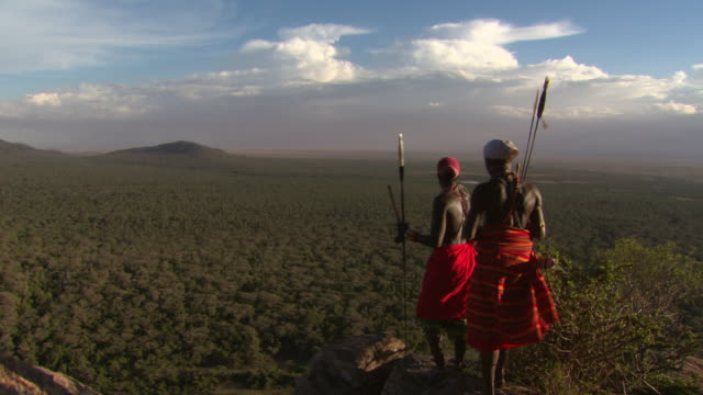 maasai or samburu two warriors stand at high point looking over amazing african landscape - krieger menschliche tätigkeit stock-videos und b-roll-filmmaterial