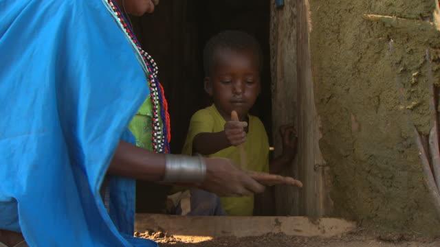maasai or samburu woman washing hands with sand and water, with audio - hut stock videos & royalty-free footage