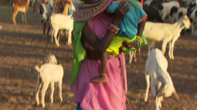 Maasai or Samburu Woman with baby, surrounded by goats, WITH AUDIO