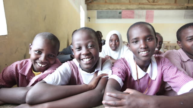 vídeos de stock e filmes b-roll de maasai school children sit at their desks in a classroom in kenya. - áfrica