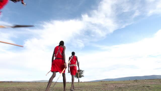 Maasai tribesmen walk across an arid landscape in Kenya.