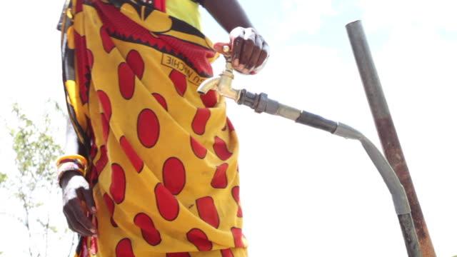 a maasai woman drinks from a tap in kenya. - stamm stock-videos und b-roll-filmmaterial
