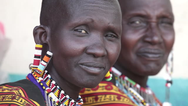 Maasai women wear colorful earrings and necklaces as they visit with each other.