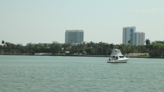 MacArthur Causeway over Biscayne Bay yachts moored to docks mansions bushes FG skyscrapers BG REFRAMING