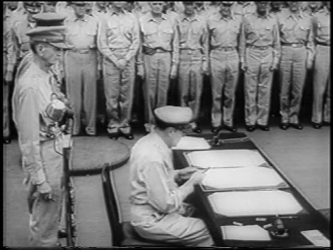 macarthur signing documents at japan's surrender / wainwright + percival stand behind him - britisches militär stock-videos und b-roll-filmmaterial